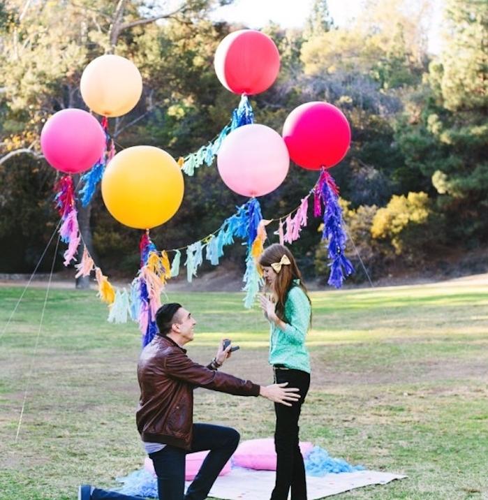 demande en mariage originale au milieu d un pré dans la forêt, couverture sur terre, coussins, ballons et pompons colorés