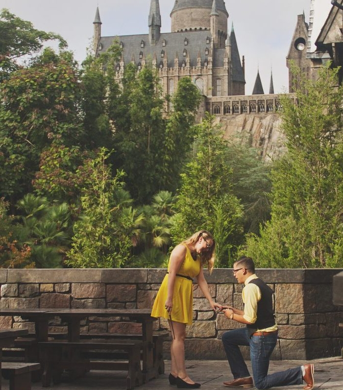 demande en mariage romantique devant un château du moyen age, femme robe jaune et homme, arbres verts