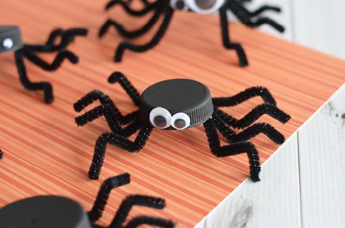 activité halloween maternelle avec bouchon couvercle bouteille noir, pieds en cure pipe et des yeux mobiles