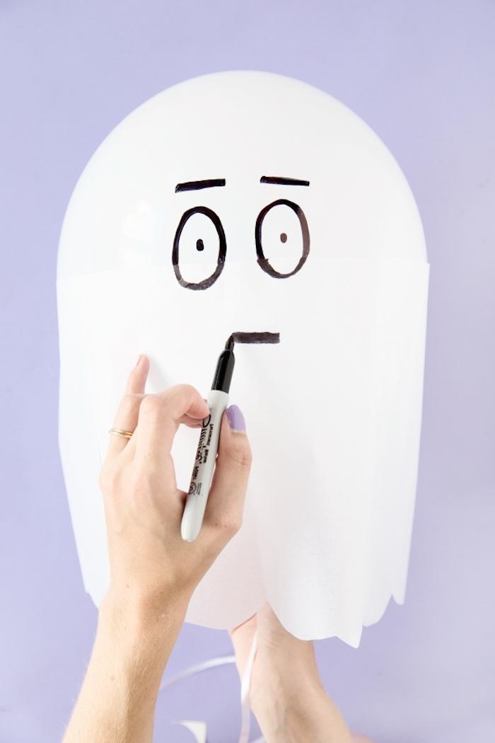 activité halloween maternelle, spectres, fantômes blancs en ballon blanc et serviette blanche et des traits de visage noirs dessinés au feutre noir