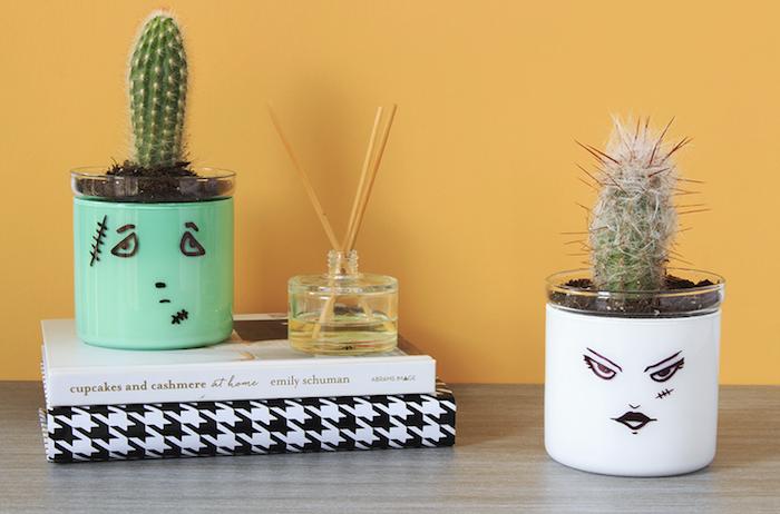 bricolage halloween avec des pots en verre repeints a l interieur et des dessins visage traits noirs a l exteireur, cactus
