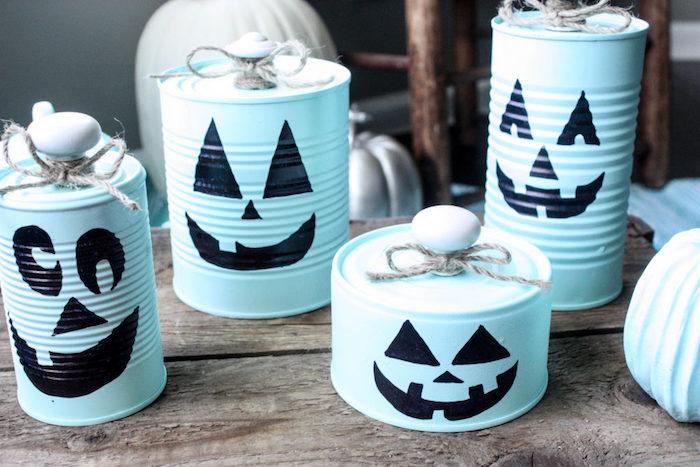 des boites de conserve repeinte en bleu avec dessin jack o lantenr à la peinture noire, activité manuelle halloween facile