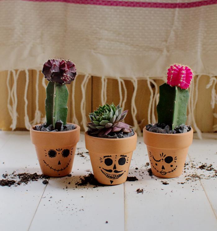 activité halloween avec des pots en terre cuite avec dessin têtes effrayantes en traits noirs, cactées