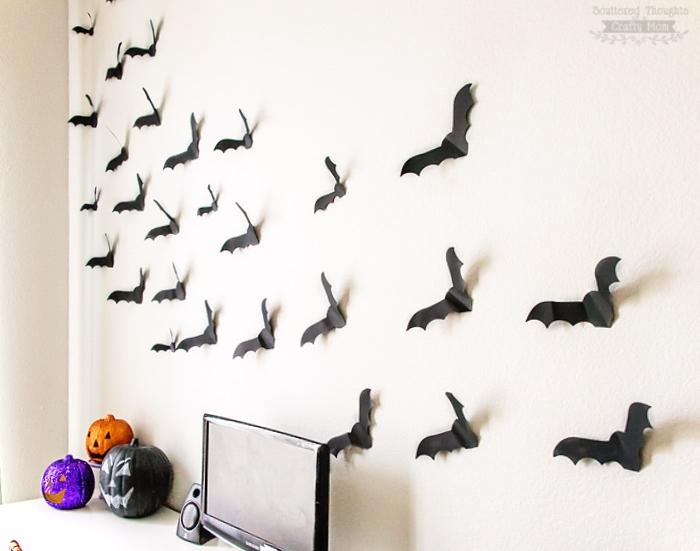 silhouettes de chauves souris en papier noir sur un mur, deco bureau avec des citrouille halloween repeinte, activite manuelle facile
