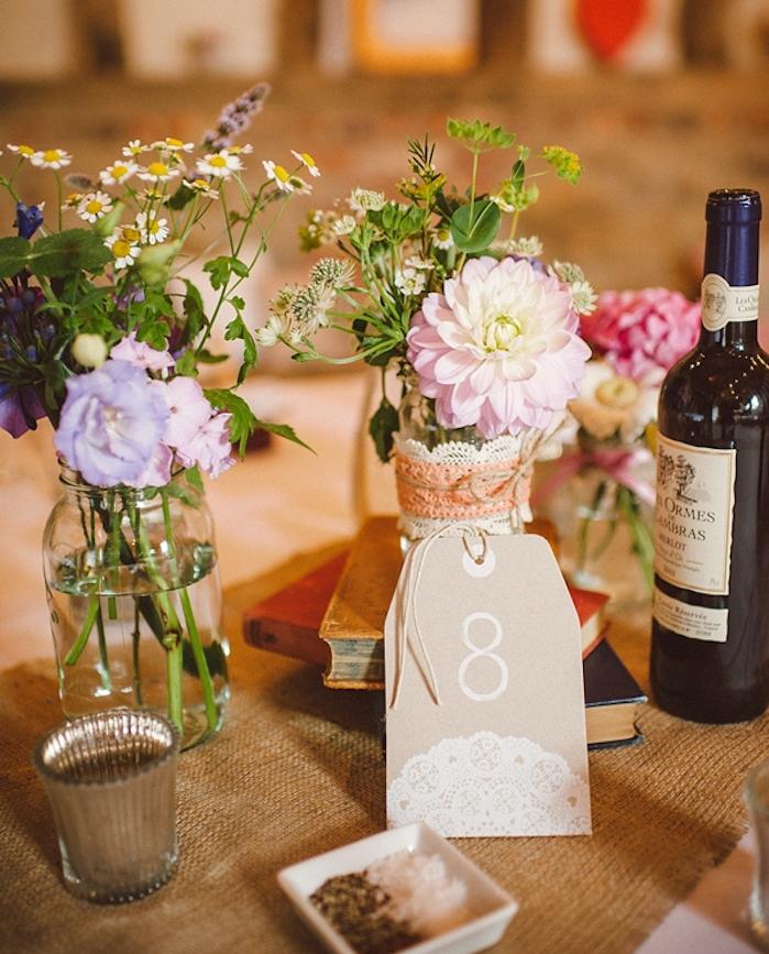 decoration table mariage, chemin de table en jute, bouquins vintage, pots en verre transformés en pots de fleurs