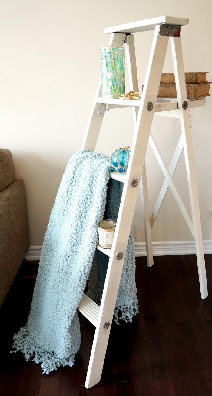 echelle bois deco, repeinte en blanc, couverture vleue, bouquins vintage et vase coloré, accents décoratifs dans un salon vintage