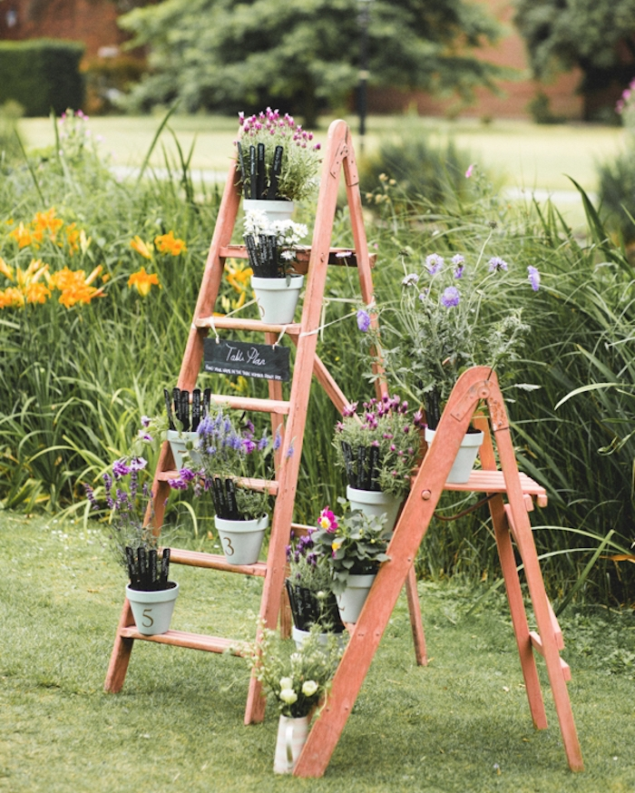 échelle décorative bois, idée de plan de table mariage avec des pots de fleurs blanches liste invités écrits sur des batonnets de glace