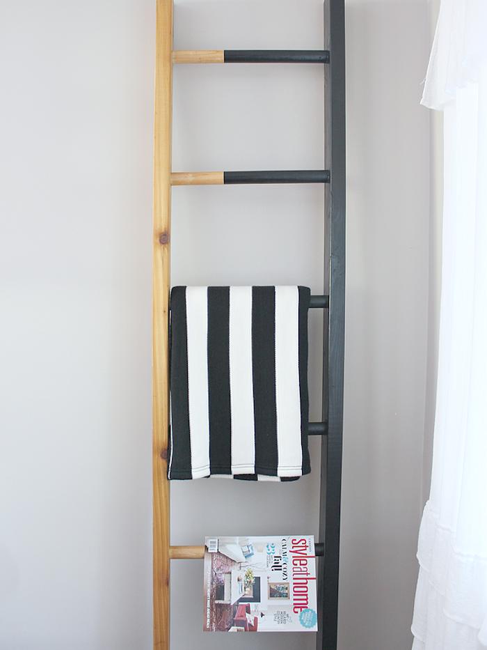 echelle deco bois, à moitié repeint en noir, range magazines et textiles, point focal dans un salon moderne