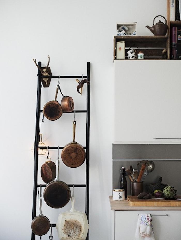 echelle decorative en metal noir pour la cuisine, ustensiles de cuisine, plan de travail bois, façade cuisine blanche