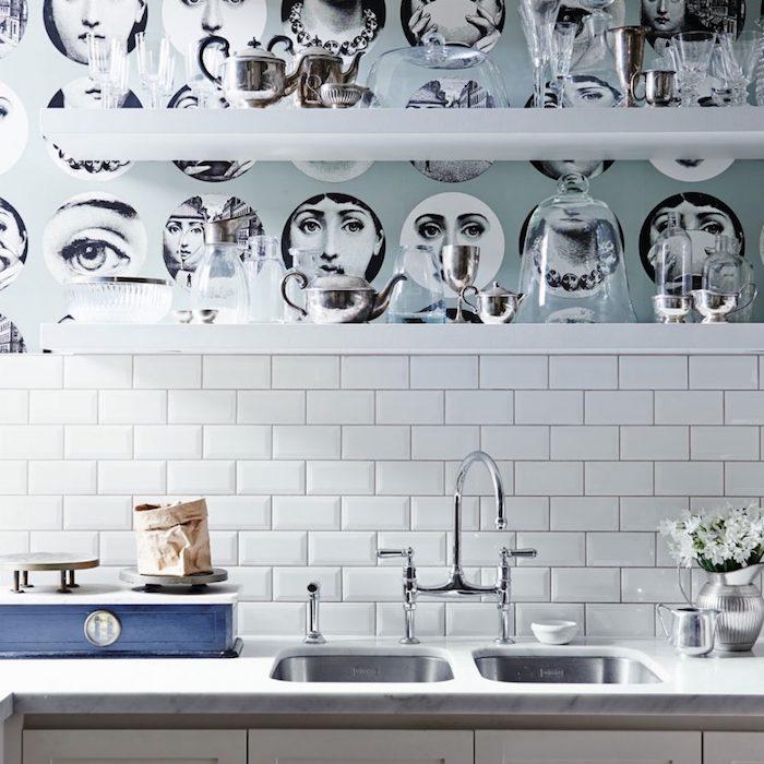 étagères blanche avec un fond customisé de papier peint, motifs visages femmes noir et blanc, carrelage crédence blanc, plan de travail marbre