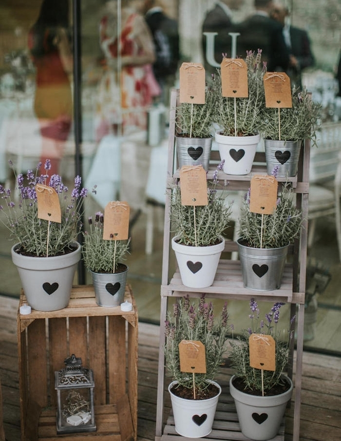 echelle deco en bois brut et cagette de bois avec des pots de fleurs, décorés de fleurs noires, étiquettes en papier kraft