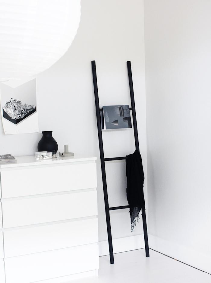 deco salon scandinave, echelle decorative noire, rangement magazines et textiles, meuble blanc et fond mur blanc