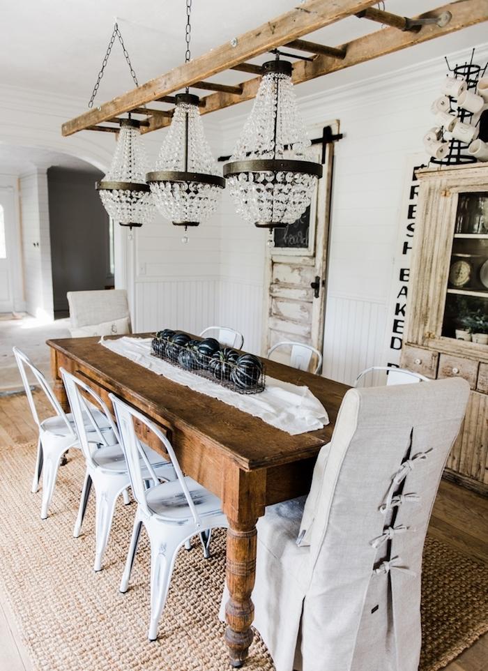 echelle bois deco, exemple d echelle suspendue du toit par des chaînes, façon rustique, lustres somptueux, table en boir rustique, chises metalliques repeintes en blanc, vaisselier patiné