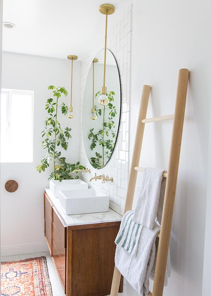 echelle porte serviette en bois clair dans la salle de bain, miroir rond, meuble sous vasque bois, plante verte, tapis oriental