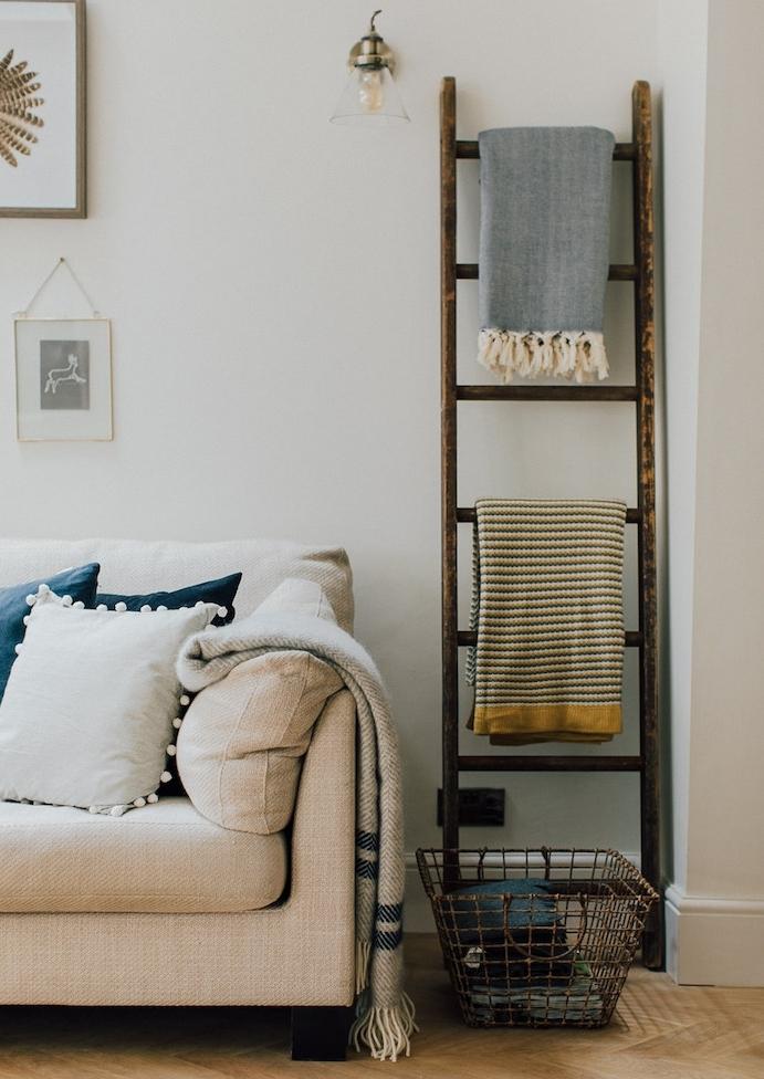 echelle porte serviette, aspect usé, rangement textiles, couvertures, canapé beige, coussins blanc et bleu, panier de rangement