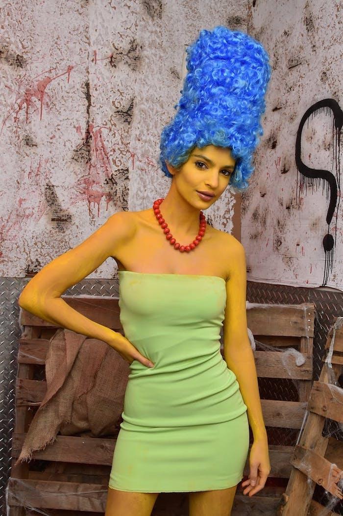 emily ratajkovski dans le role de marge simpson, corps coloré en jaune, perruque bleue, collier rouge et robe verte, halloween deguisement facile