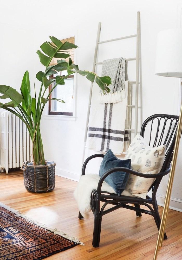 deco scandinave, parquet en bois clair, chaise noire, plante verte, tapis oriental et échelle décorative bois, rangement textiles, couvertures