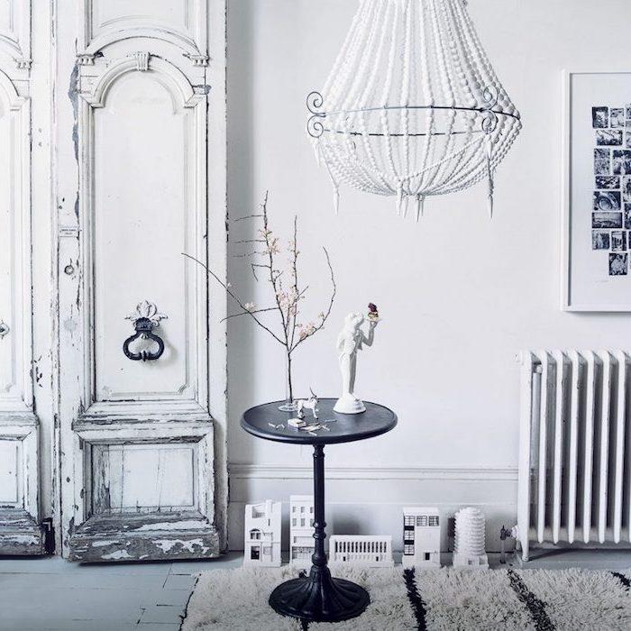 comment patiner un meuble, idée intérieur vintage en blanc, armoire blanche patinée pour faire ressortir une couche grise, table s appoint noire, lustre élégant, tapis noir et blanc
