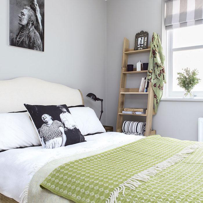 echelle etagere en bois avec des rangements avec accessoires deco et livres, linge de lit blanc, couverture vert pistache, deco murale graphique