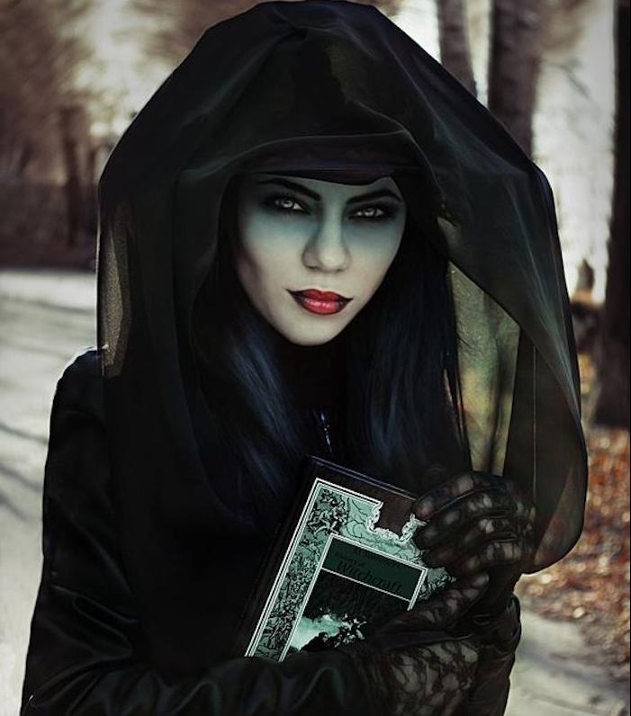 exemple de déguisment femme halloween sorcière, peau teinte verte, chapeau, robe et cape noirs, grimoir, rouge a lèvres foncé