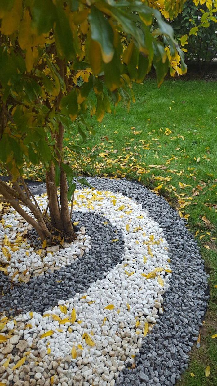 parterre de fleurs, gazon vert couvert de feuilles orange et jaunes, déco jardinage en cailloux blancs et noirs