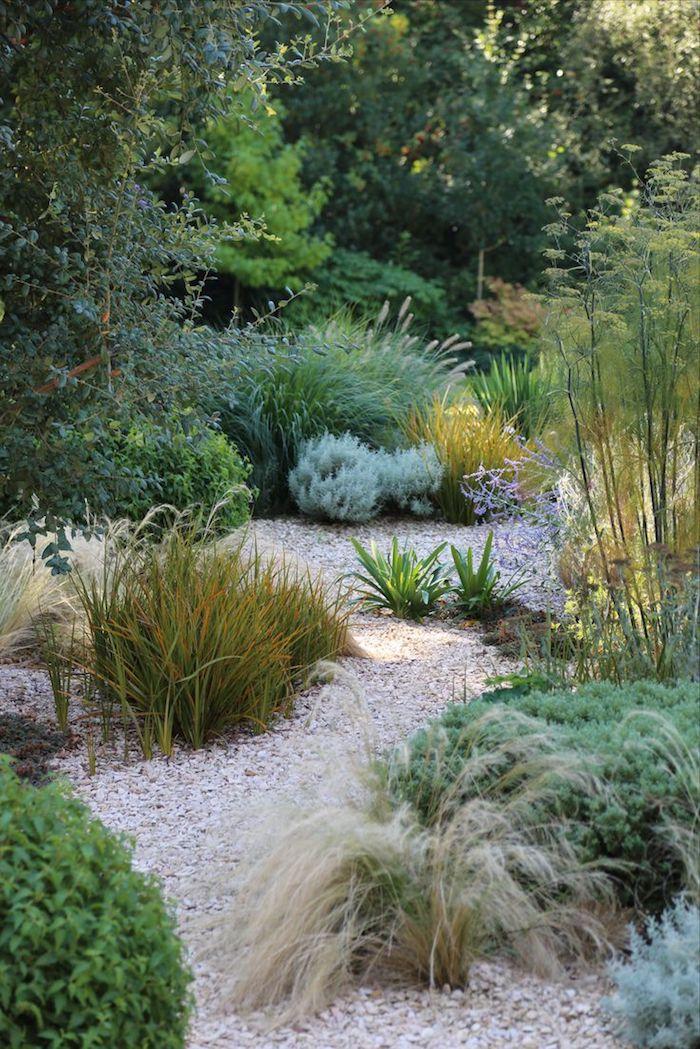 parterre de fleurs, cailloux et galets avec plantes vertes, déco de jardin inspiration nature sauvage