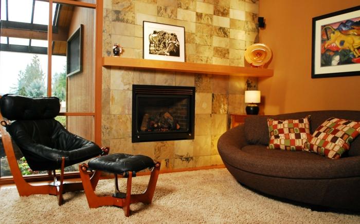 idee deco salon cocooning, chaise noire en cuir avec un taboret, papier peint pierre apparente, canapé marron, tapis beige