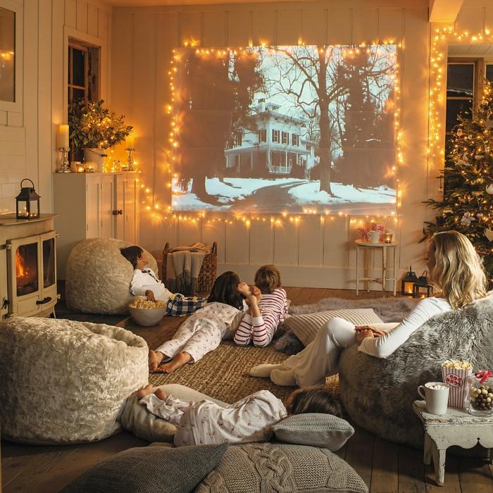 idée déco salon, cheminée ancienne peinte blanche, sapin de Noel, poufs moelleux, tapis sisal, lanternes et grand écran de projection