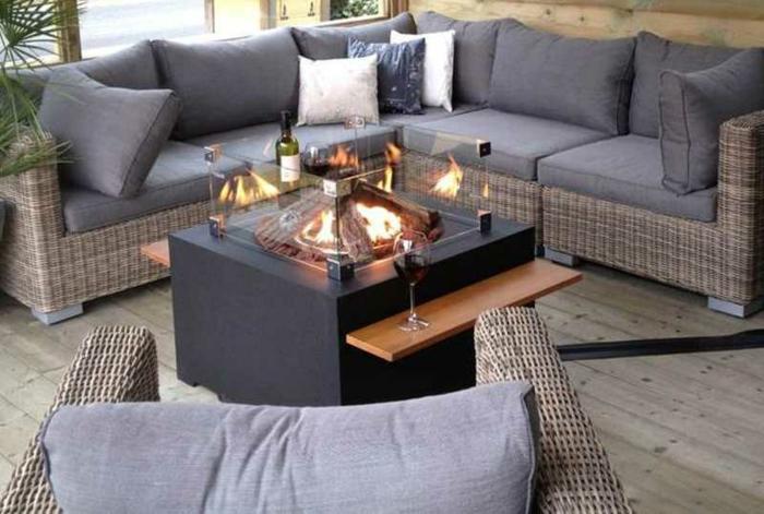 idée déco salon, canapés en rotin, table noire originale, sol en planches de bois