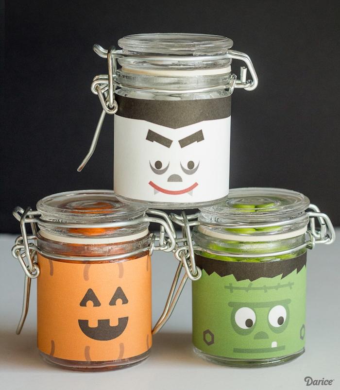 activité halloween avec des pots en verre, décorés de papier avec des visages monstre, vampire e jack o lanterne, bougeoir halloween