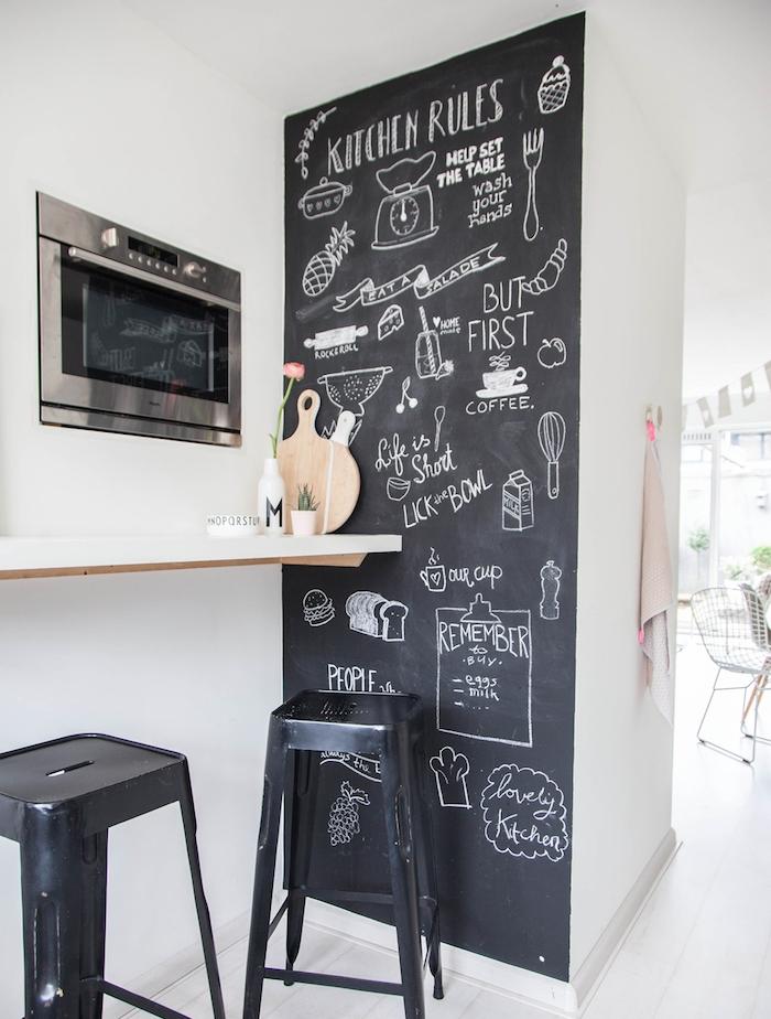 idée de mur repeint en peinture ardoise pour tableau noir, dessins planning à la craie, tabourets metalliques noires, carrelage blanc, refaire sa cuisine