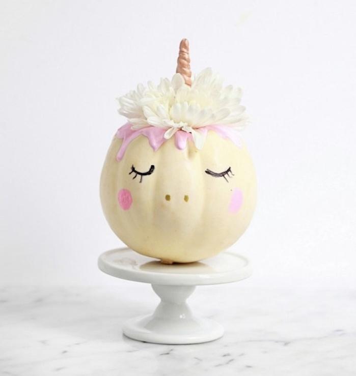 citrouille halloween blanche transformé en licorne avec des yeux dessinés au feutre noir, joues rose, fleurs blanche en guise de cheveux, peinture rose et corne, décoration halloween a fabriquer