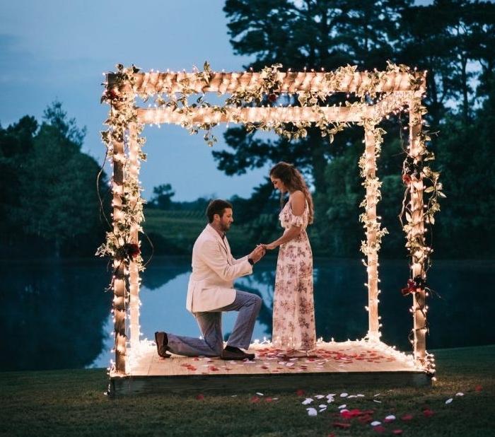 idée demande de fiancaille originale sur une pergola en bois, au bord d un lac, guirlande lumineuse et fleurs