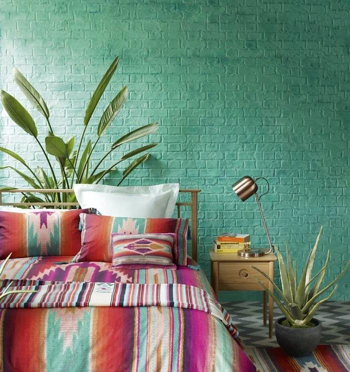 couleur chambre adulte, mur en briques repeint en vert, linge de lit boheme chic à motifs colorés, revetement sol gris et blanc, lampe design, plantes vertes