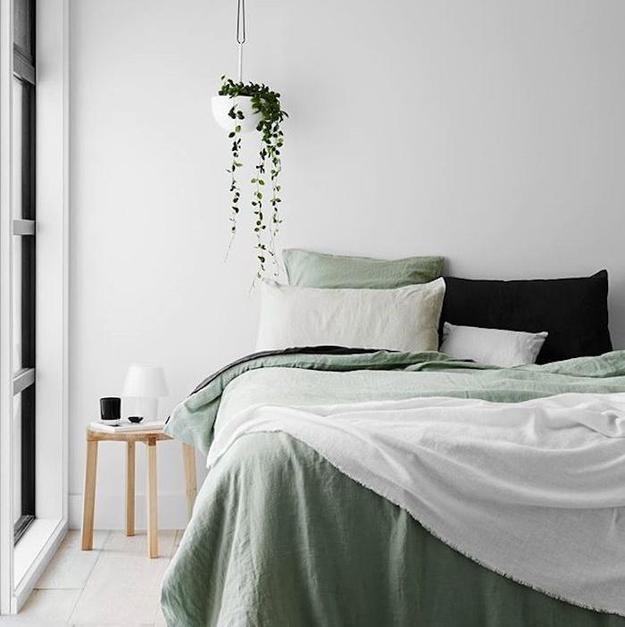 décoration chambre adulte, mur couleur blanche, linge de lit blanc et vert, coussin noir, parquet clair, table de nuit bois, plante verte suspendue