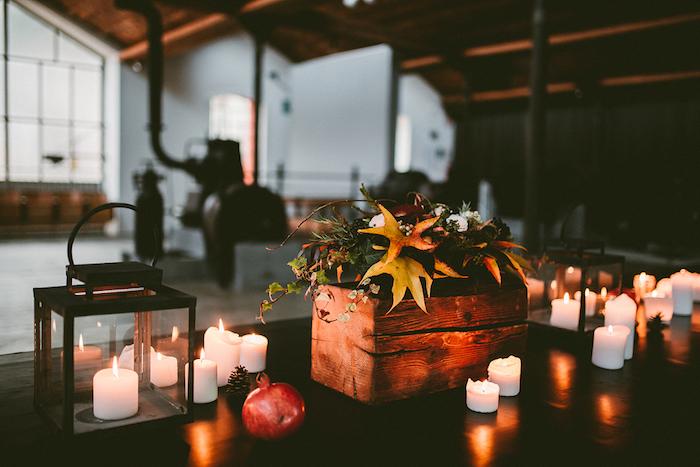 idee deco mariage automne avec un bac en bois avec des fleurs en guise de centre de table, bougies, lanterne noire, pomme de pin