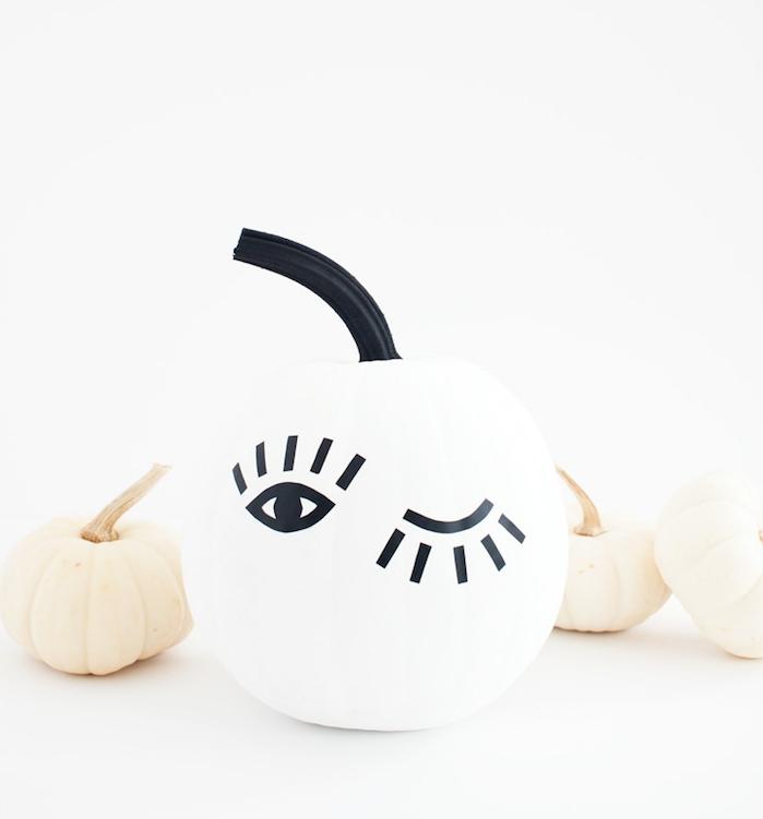 citrouille, repeinte en blanc avec des yeux graphiques noires, idee deco halloween a faire soi meme intéressante