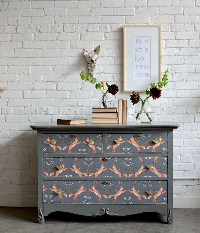 idée comment decorer une vieille commode à la patine meuble et papier peint motif renard, bouquins et bouquets de fleurs, mur en briques blanches