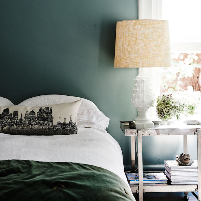 couleur chambre adulte, vert foncé, linge de lit blanc et vert, coussins avec imprimé paysage urbain, etagere metallique design