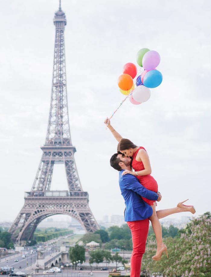 demande en mariage romantique au pied de la tour eiffel, une vue magnifique, couple homme et femme avec des ballons
