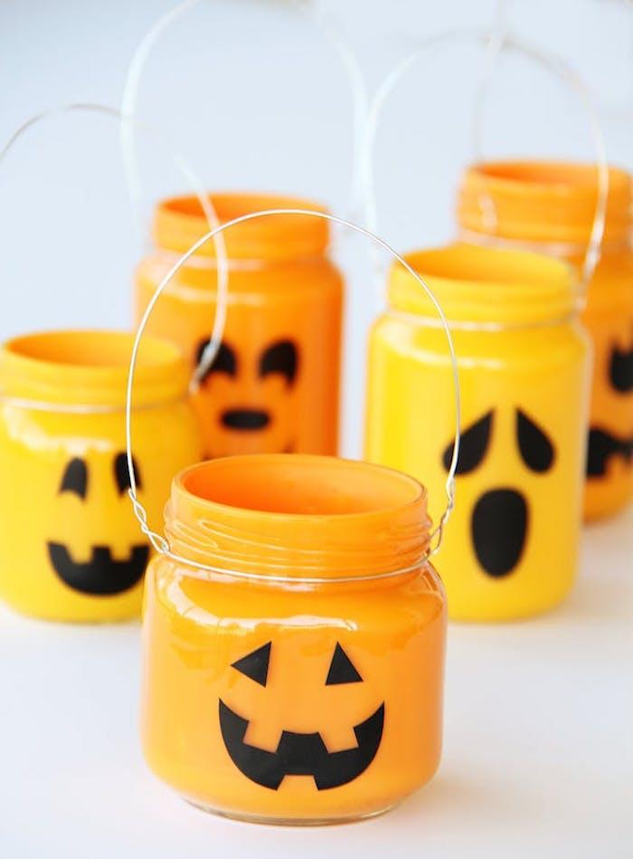 bricolage halloween avec des pots en verre, repeints de peinture orange à l interieur et des traits de visage noirs jack o lantern a l exterieur