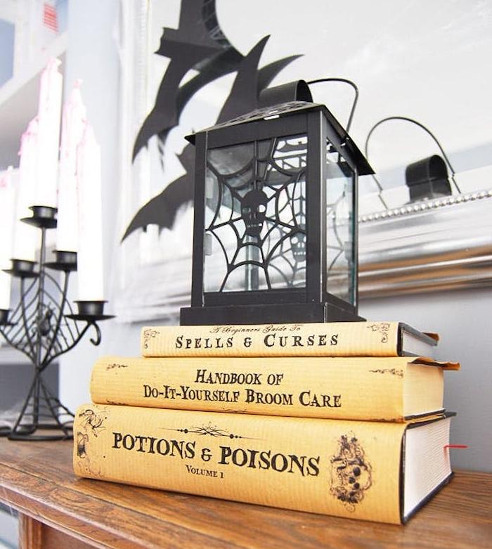 activite halloween, une lanterne noire avec des livres sorcellerie entassés, bougeoir noir et des silhouettes chauve souris en papier