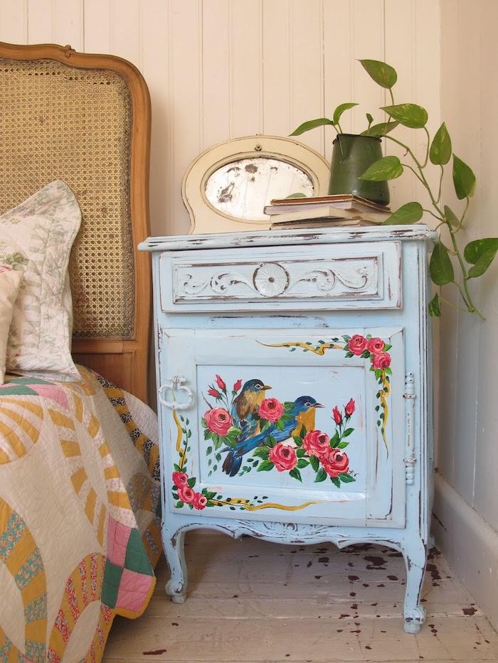 idée comment renover un meuble, table de nuit repeinte en bleu pastel avec dessin oiseaux et motifs floraux, parquet blanchi, lit vintage, plante verte
