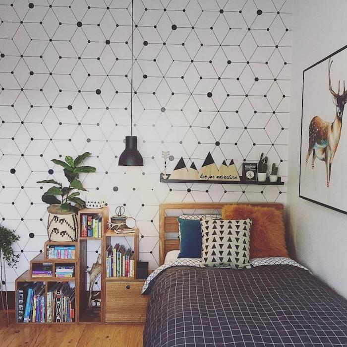 modele de papier peint graphique scandinave, lit bois, linge de lit blanc et gris, étagère rangement bois, suspension noire et peinture cadre cerf