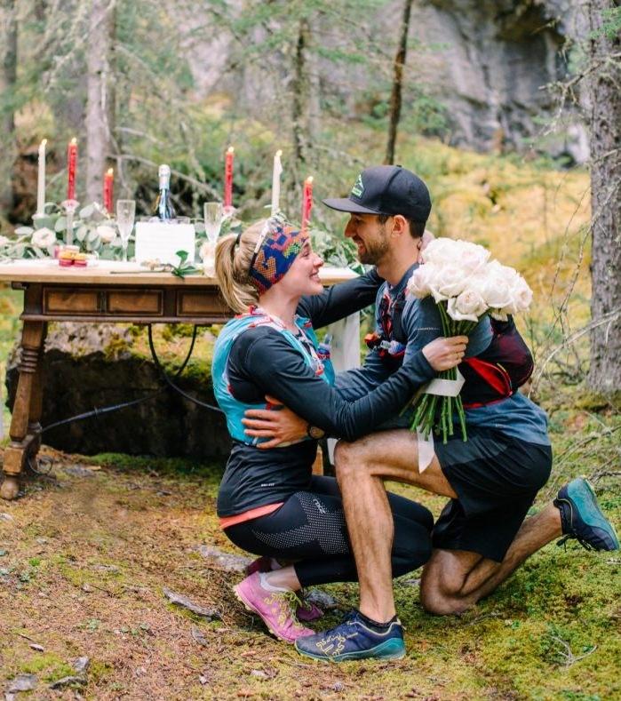 randonnée dans la montagne qui finit par une demande en mariage originale, table en bois, bougies, champagne, femme et homme en tenue sportive