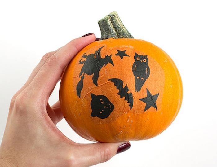 decoupage silhouettes noires, sorcière, chat noir, hibou, etoiles et chauve souris sur une citrouille orange miniature