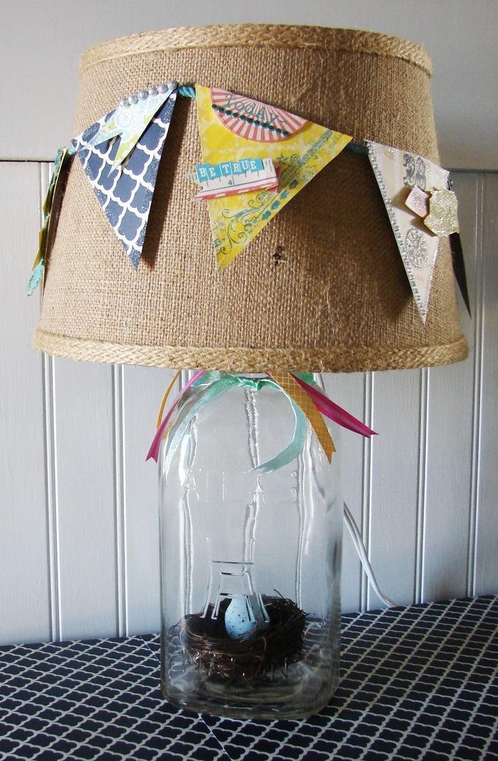 une lampe à poser avec abat-jour décoré de fanions et support bocal contentant un nid doiseau décoratif
