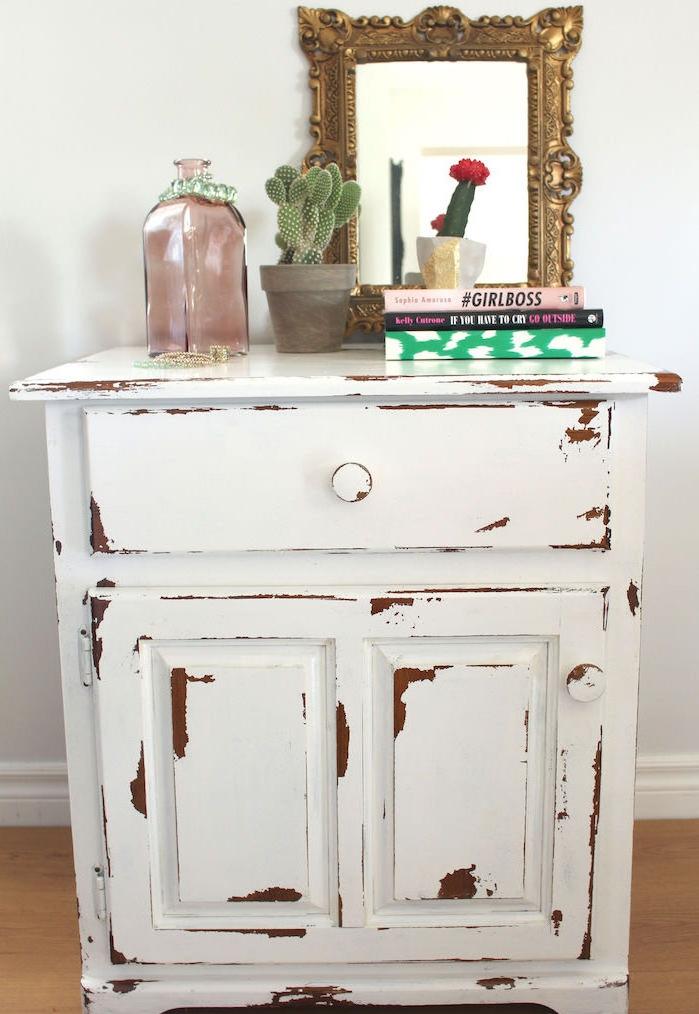 patiner un meuble, idée de petite table rangement en bois, peinture couleur blanche, livres, plante, miroir baroque et bouteille deocrative