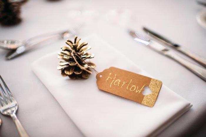 deco mariage pas cher, pomme de pin repeinte de couleur or avec étiquette en papier kraft doré sur une serviette blanche