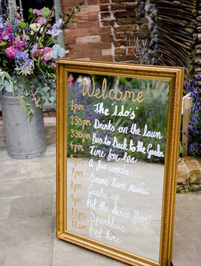 idée programme de mariage dans un miroir avec emploi de temps écrit sur le verre au feutre blanc et doré, bouquet de fleurs, cadre or